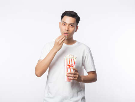 Young asian man in white t-shirt holding and eating popcorn with happy face isolated on white background. Zdjęcie Seryjne