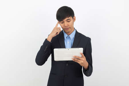 Young handsome asian business man using tablet computer with doubts isolated on white background. Zdjęcie Seryjne
