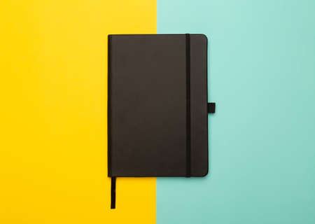 Black notebook isolated on yellow and blue background. Flat lay or Top view angle.