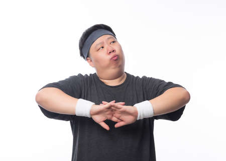 Asian funny fat man in sport outfits make streching before workout and looking to copyspace isolated on white background. Zdjęcie Seryjne
