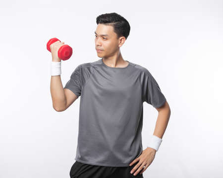 Young handsome asian man in sport outfits exercising with dumbbell isolated on white background. Zdjęcie Seryjne