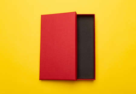 Red box product packaging isolated on yellow background. Zdjęcie Seryjne