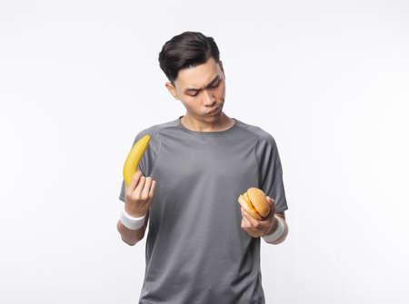 Young handsome asian sport man holding banana and hamburger with doubts face isolated on white background. Zdjęcie Seryjne