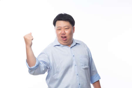 Young Fat Asian business man raising his fists with funny face isolated on white background. Zdjęcie Seryjne