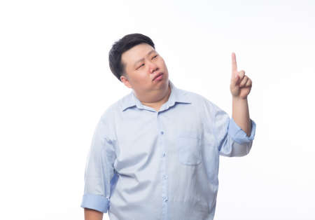 Asian Fat Man in blue shirt thinking and pointing to copyspace with doubts face isolated on white background.