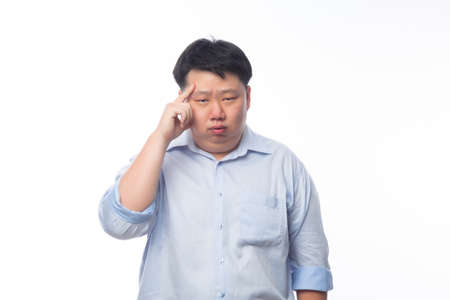 Young Fat Asian business man thinking with doubts face isolated on white background. Zdjęcie Seryjne