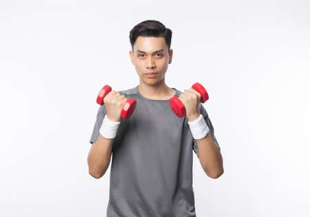 Young handsome asian man in sport outfits exercising with dumbbells and looking to camera isolated on white background.