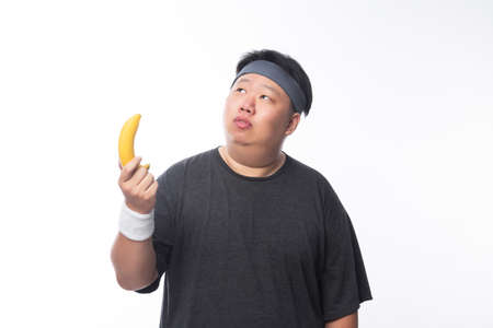 Young Asian funny fat sport man holding banana isolated on white background. Healthy lifestyle concept.