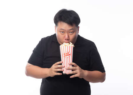 Funny young asian fat man in black polo shirt eating popcorn isolated over white background.