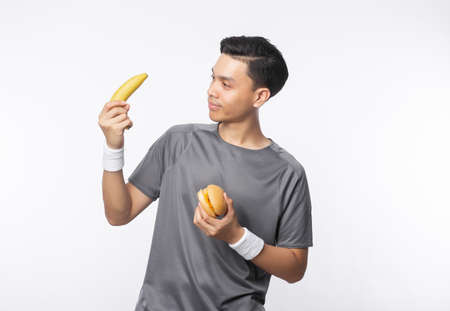 Young handsome asian sport man holding banana and hamburger with smiling isolated on white background.