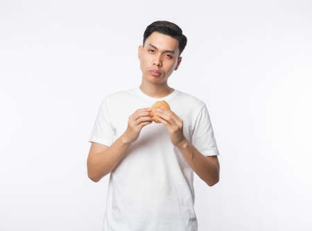 Young asian man in white t-shirt eating hamburger with happy face isolated on white background. Zdjęcie Seryjne