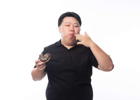 Happy young asian fat man in black polo shirt eating donut isolated over white background.