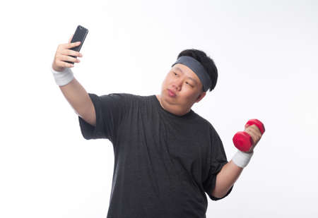 Young Asian funny fat sport man exercise with dumbbell and using smartphone take a selfie isolated on white background. Zdjęcie Seryjne