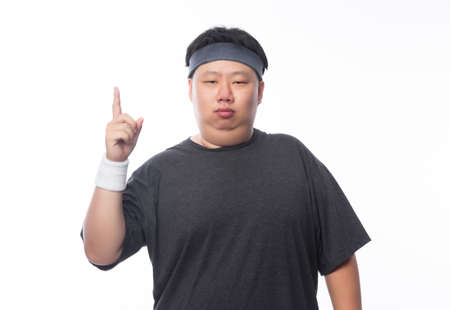 Young Asian funny fat sport man poiting to copy space isolated on white background.