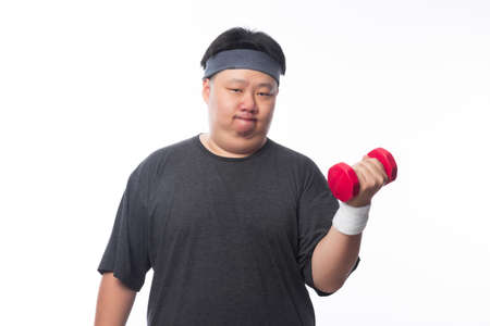 Young Asian funny fat sport man exercise with dumbbell isolated on white background. Zdjęcie Seryjne