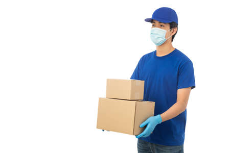 Young Delivery man wearing mask and medical gloves holding paper cardboard box mockup isolated on white background Zdjęcie Seryjne
