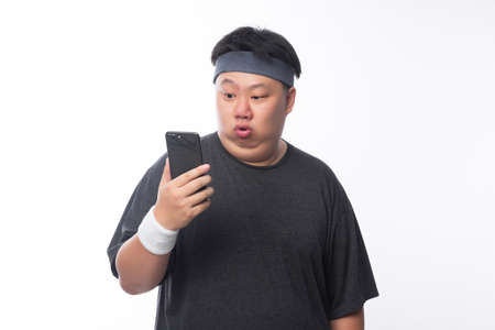 Asian funny fat man in sport outfits using smartphone while break from exercise isolated on white background.