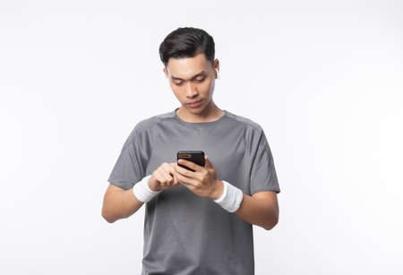 Young handsome asian man in sport outfits using phone and listening music with smiling isolated on white background. Zdjęcie Seryjne
