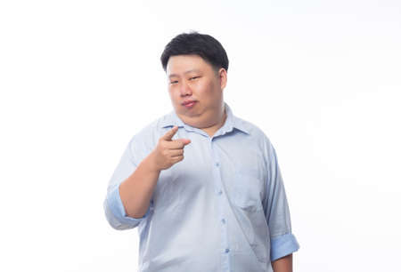 Young Fat Asian business man poiting to camera with funny face isolated on white background.