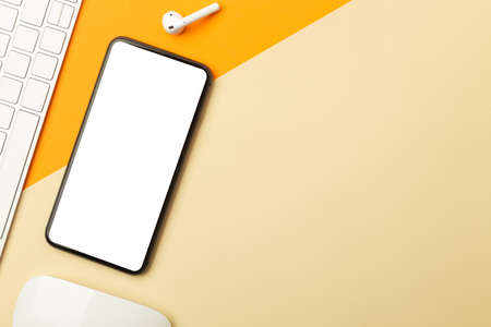 Flat lay, top view of orange office table desk with smartphone blank screen mockup with
