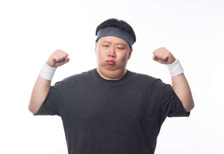 Young Asian funny fat sport man showing strenght isolated on white background. 版權商用圖片