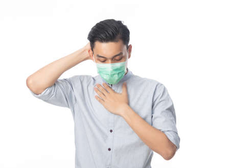 Young Asian businessman in hygienic mask suffering sore throat and having flu, 2019-nCoV or coronavirus. Airborne respiratory illness such as pm 2.5 fighting. Studio shot isolated on white background.