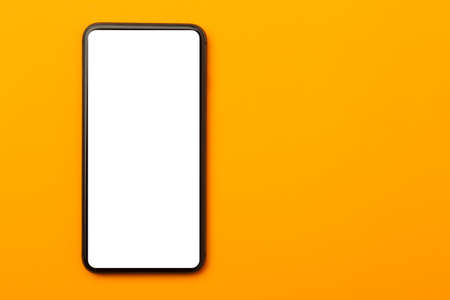 Flat lay, top view of orange office table desk with smartphone blank screen mockup