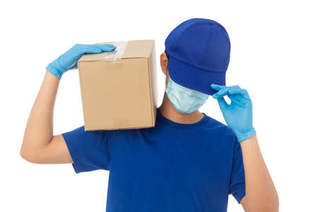 Young Delivery man wearing mask and medical gloves holding paper cardboard box mockup isolated on white background 版權商用圖片