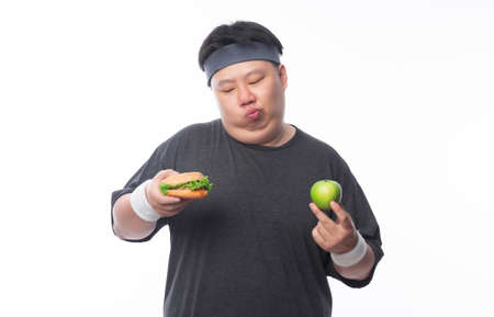 Young Asian funny fat sport man holding hamburger and green apple isolated on white background. Healthy lifestyle concept. 版權商用圖片