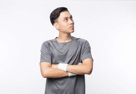 Young asian man in sport outfits arms crossed and looking to copyspace isolated on white background.