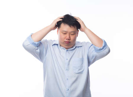 Young Fat Asian business man feeling sad with unhappy face isolated on white background. 版權商用圖片