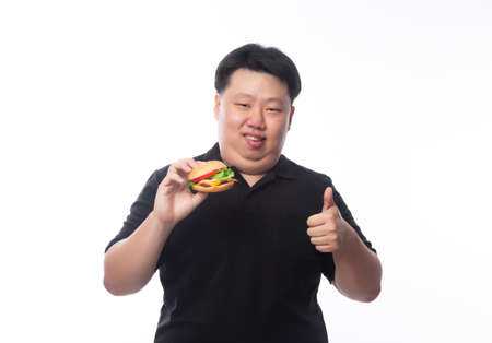 Young Funny Fat Asian man holding hamburger and showing thumbs up isolated on white background, Unhealthy concept.