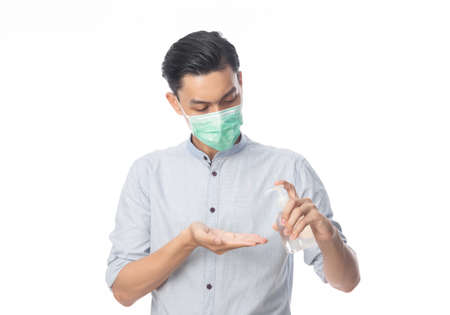 Young Asian Businessman wearing hygienic mask and using hand sanitizer or alcohol gel