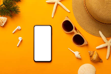 Summer background with blank screen phone and beach accessories - sunglasses, straw hat on vibrant orange background top view with copy space. Zdjęcie Seryjne