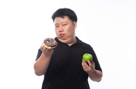 Young Funny Fat Asian man choosing between chocolate donuts and green apple isolated on white background, Healthy lifestyle concept.