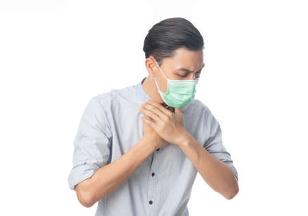 Young Asian Businessman in hygienic mask suffering sore throat, 2019-nCoV or coronavirus. Airborne respiratory illness such as pm 2.5 fighting and flu. Studio shot isolated on white background.