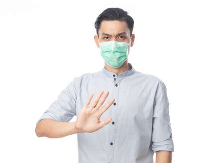 Young Asian businessman wearing hygienic mask gesturing stop to prevent infection, 2019-nCoV or coronavirus. Airborne respiratory illness such as pm 2.5 fighting and flu. Studio shot isolated on white background. 版權商用圖片