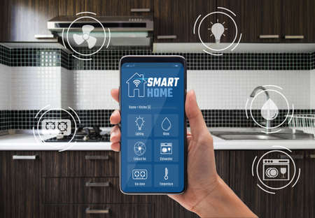 Smart home technology concept, Woman hand using application on smartphone for kitchen controlled with implements icons, Internet of things (IOT), Devices connected in home interior.
