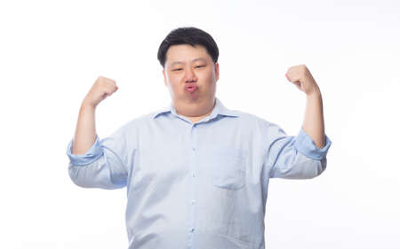Young Fat Asian business man showing strenght and looking to camera isolated on white background. Zdjęcie Seryjne