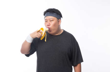 Young Asian funny fat sport man eating banana isolated on white background. Healthy lifestyle concept. 版權商用圖片