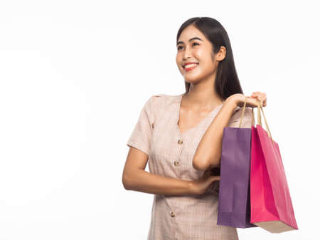 Portrait of an excited beautiful asian woman wearing dress and holding shopping bags isolated on white background.
