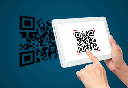 Hand using tablet computer scan Qr code on blue background. Cashless technology and digital money concept. 版權商用圖片