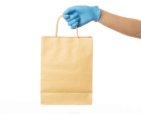 Closeup delivery man hand in medical gloves holding craft paper bag isolated on white background, Packaging mockup, Delivery service concept.
