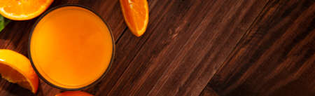 Fresh orange juice in glass and oranges fruit on wooden table banner background top view with copy space. 版權商用圖片