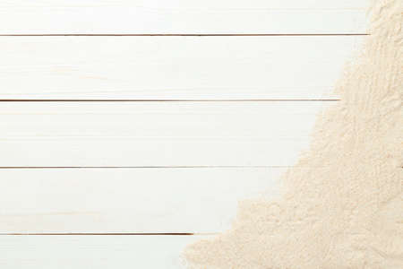 Summer background with sand on white wood table background top view with copy space. 版權商用圖片