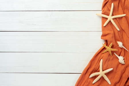 Summer background with beach objects - starfish, seashell on white wood table background top view with copy space.