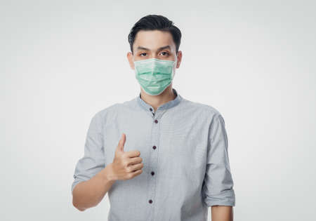 Young Asian Businessman wearing hygienic mask and showing thumb up to prevent infection, 2019-nCoV or coronavirus. Airborne respiratory illness such as pm 2.5 fighting and flu isolated on white background. 版權商用圖片