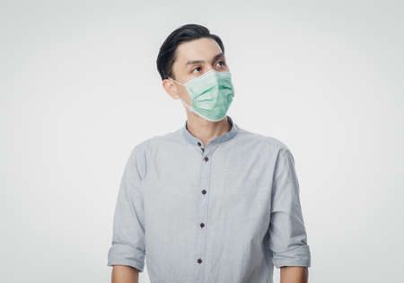 Young Asian Businessman wearing hygienic mask and looking up to prevent infection, 2019-nCoV or coronavirus. Airborne respiratory illness such as pm 2.5 fighting and flu isolated on white background.