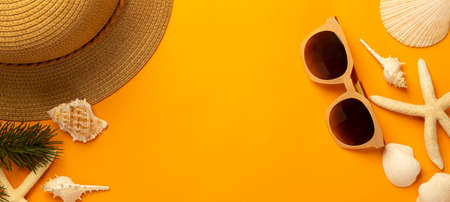 Summer background with beach accessories - straw hat, sunglasses on vibrant orange banner background top view with copy space. 版權商用圖片