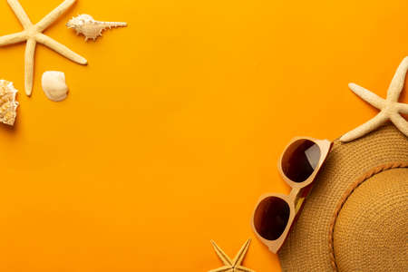 Summer background with beach accessories - straw hat, sunglasses on vibrant orange background top view with copy space.